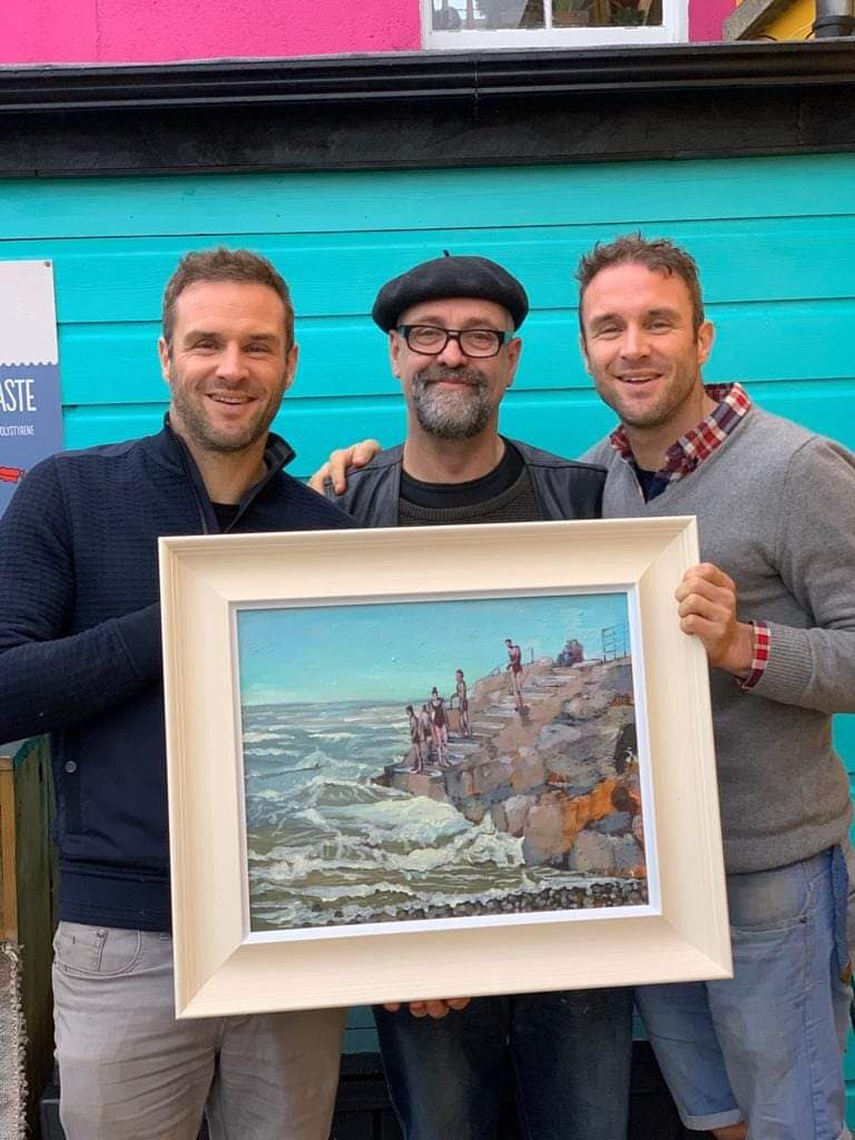 Tom Byrne with the Happy Pear Twins and his painting of their sun rise swims